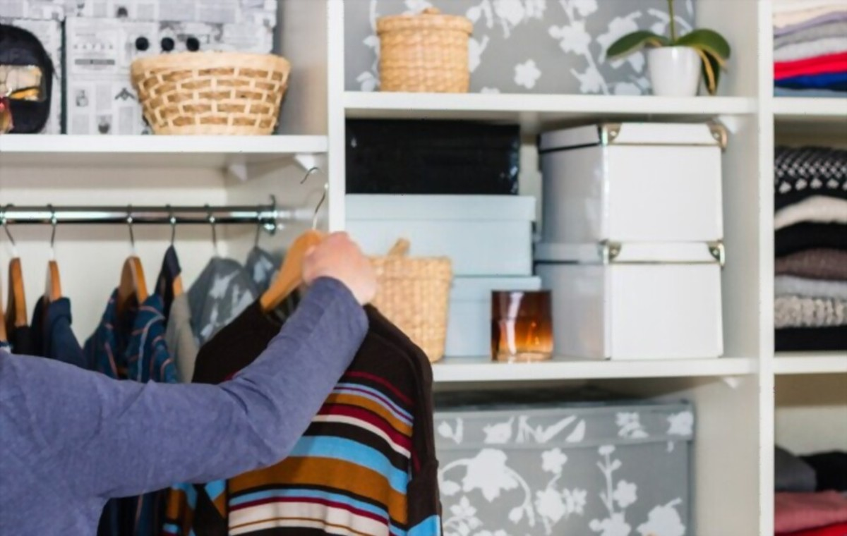 The European blond boy teenager brings wardrobe order, puts everything in its place