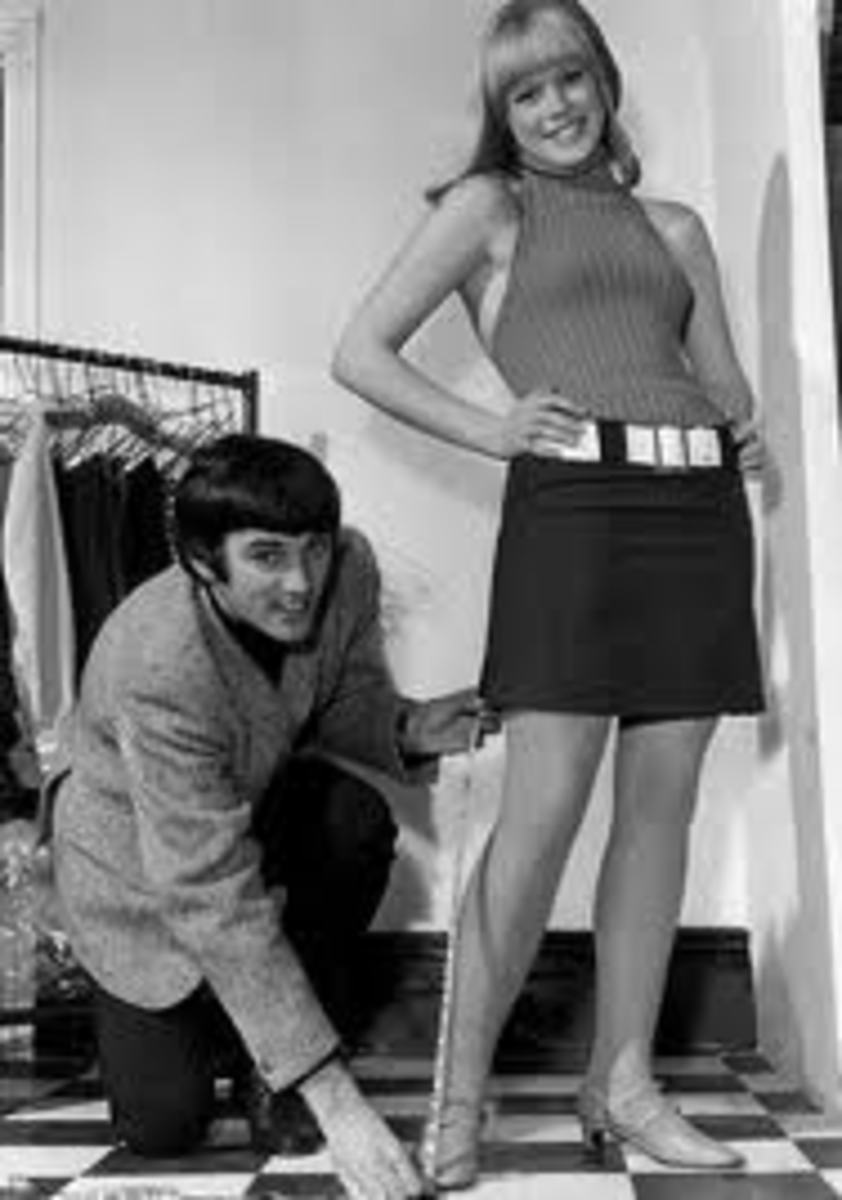 British footballer George Best measures the hemline of a Sixties model.