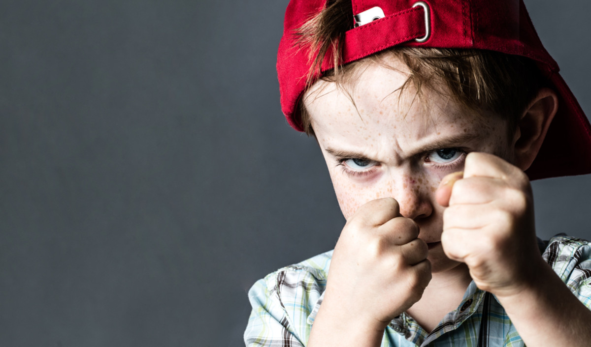 threatening 6-year old boy with freckles and a red hat back looking violent with fists in the forefront, acting like a little bully at school, contrast effects over grey background studio