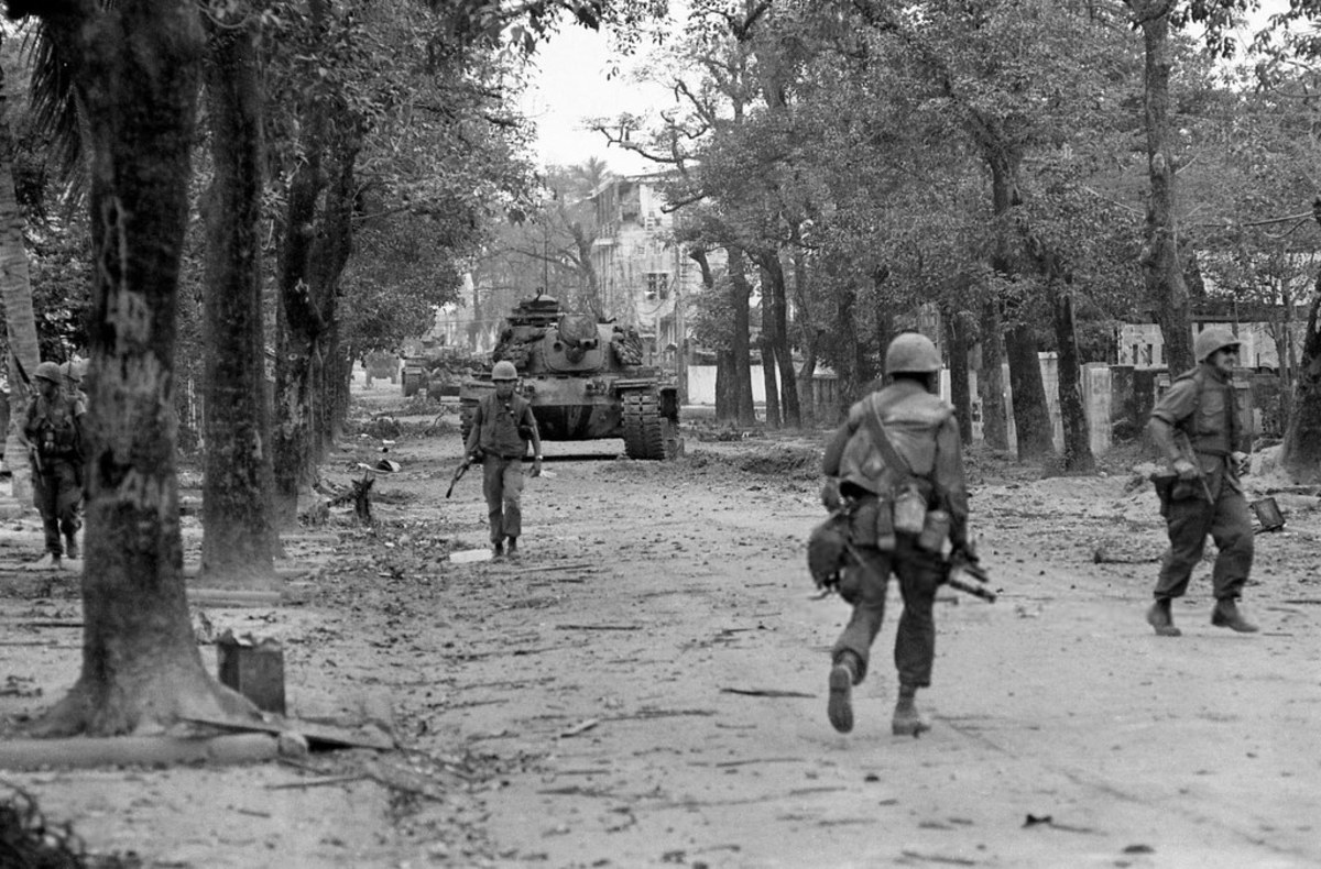 American M-60 tank rolling down the streets of Hue supporting Marines.