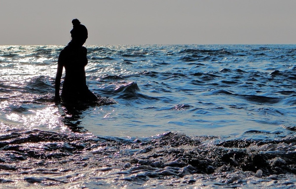 A woman wades in the ocean's vast water as she contemplates.