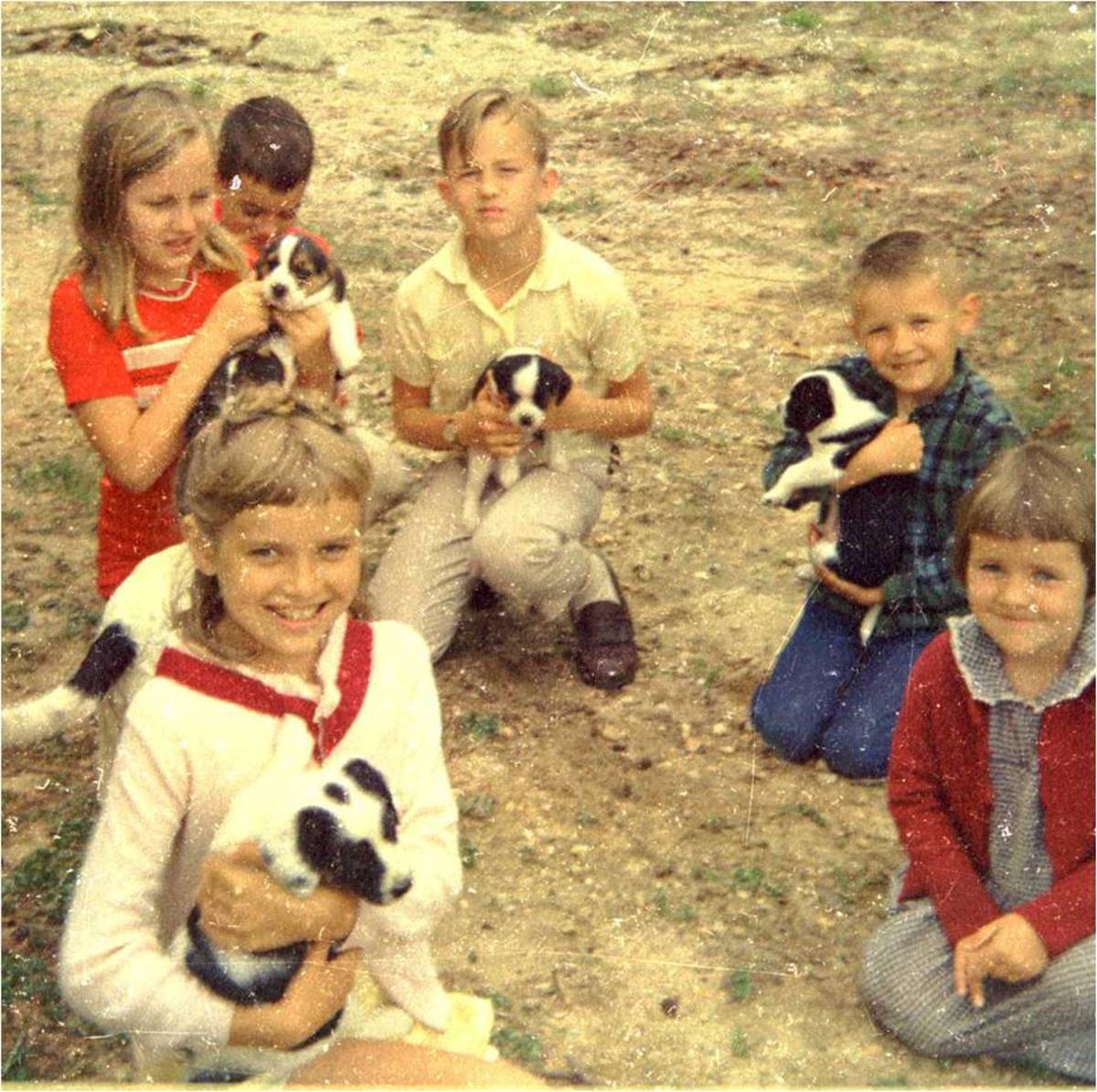 That's me, wearing a white sweater, on the front left holding a puppy.  My sister who is five years younger than me is to the front right and not holding a puppy.  My brother is behind her. The rest are friends.