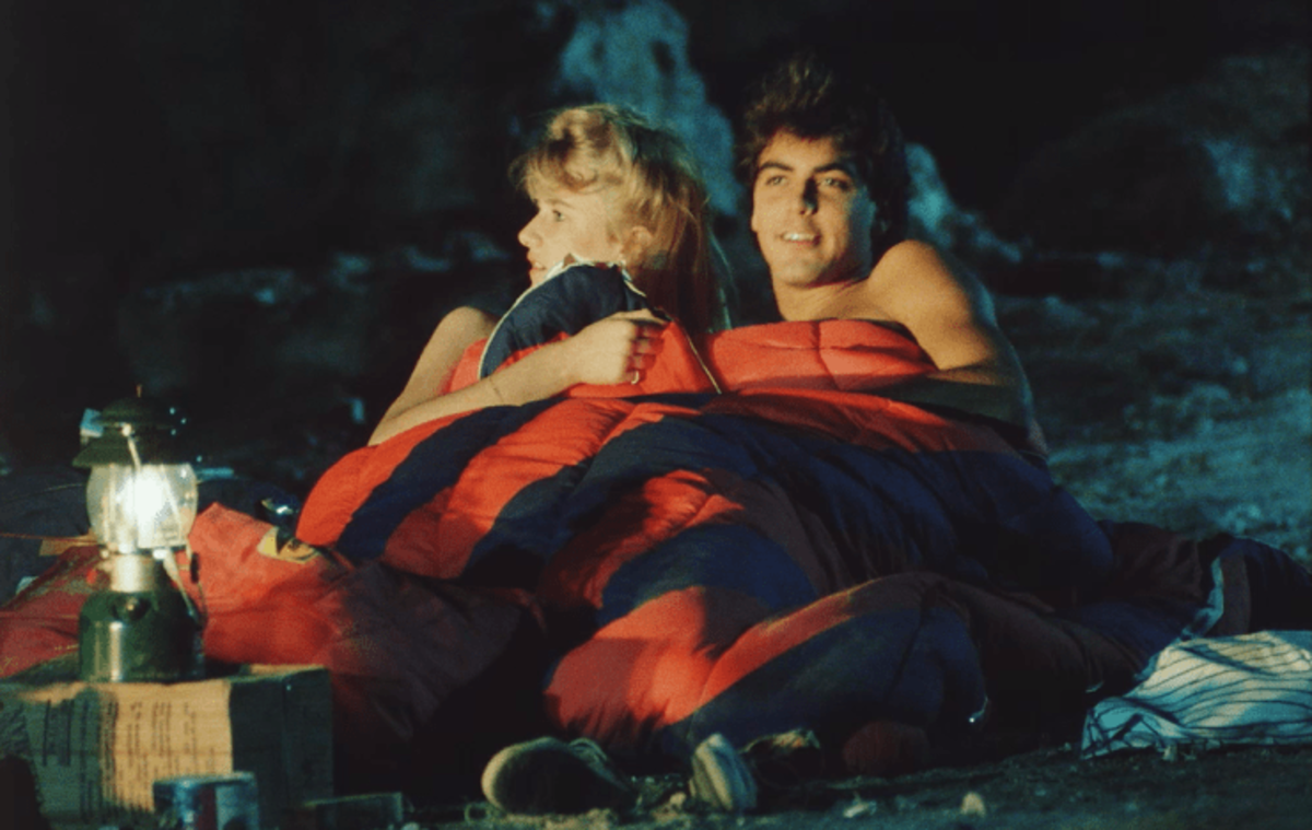 Future Oscar winners, Laura Dern and George Clooney snuggle by the campfire in Grizzly II: Revenge