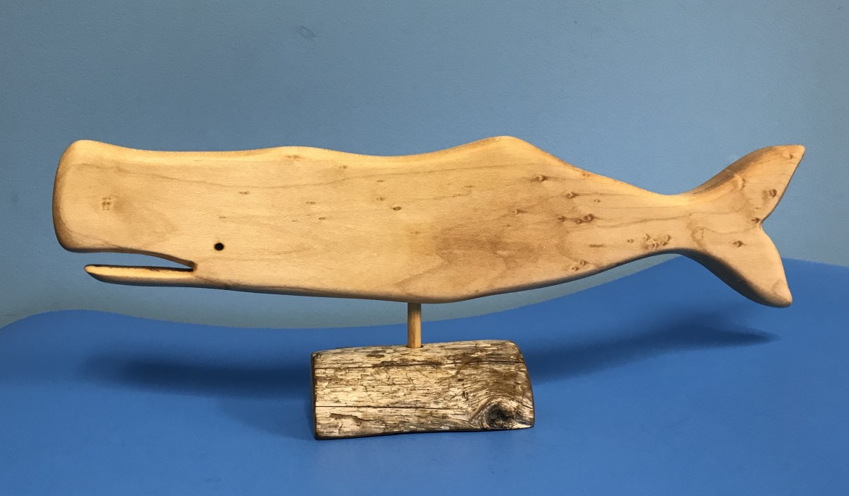 This whale is made of maple and sits on a driftwood stand