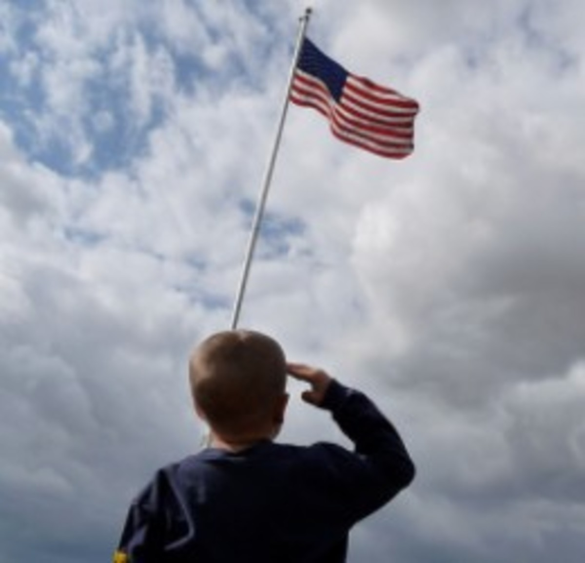 A child shows respect by saluting the red, white, and blue American flag.