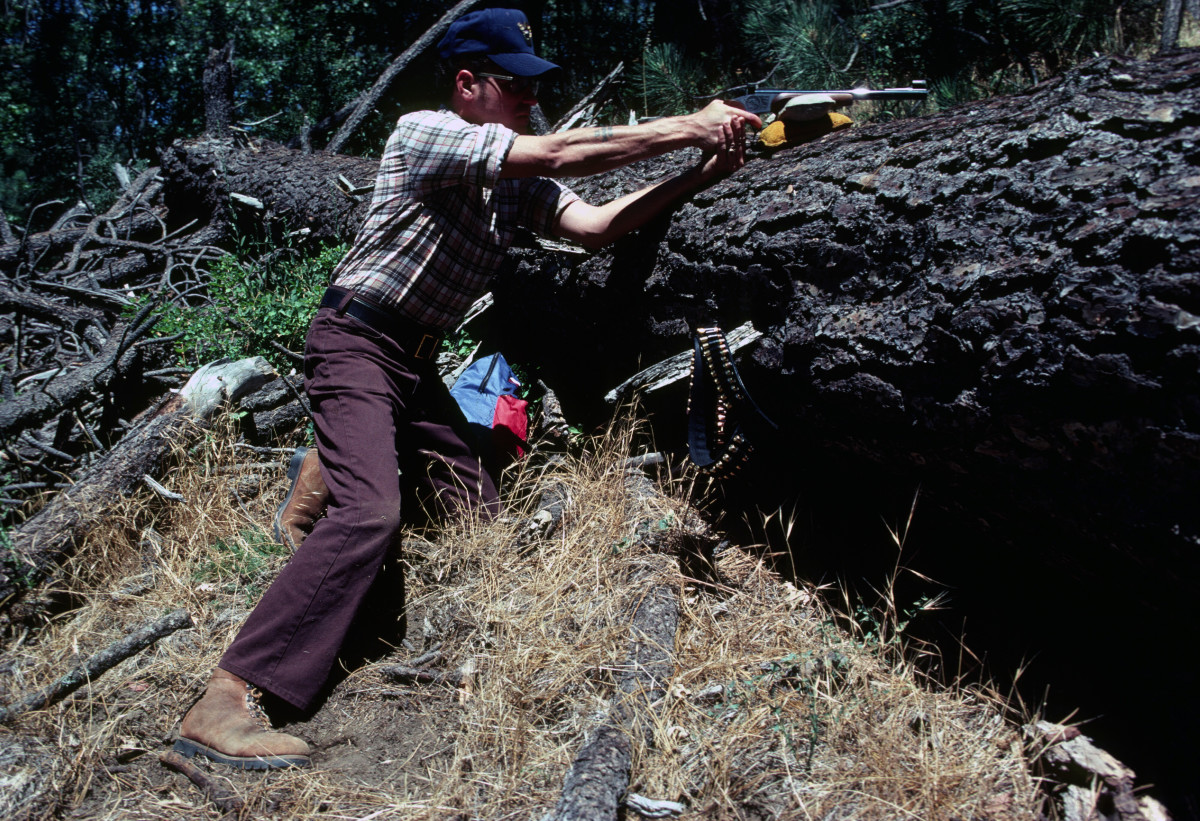 Ed uses the fallen tree and sandbag as a steadying support for his handgun.