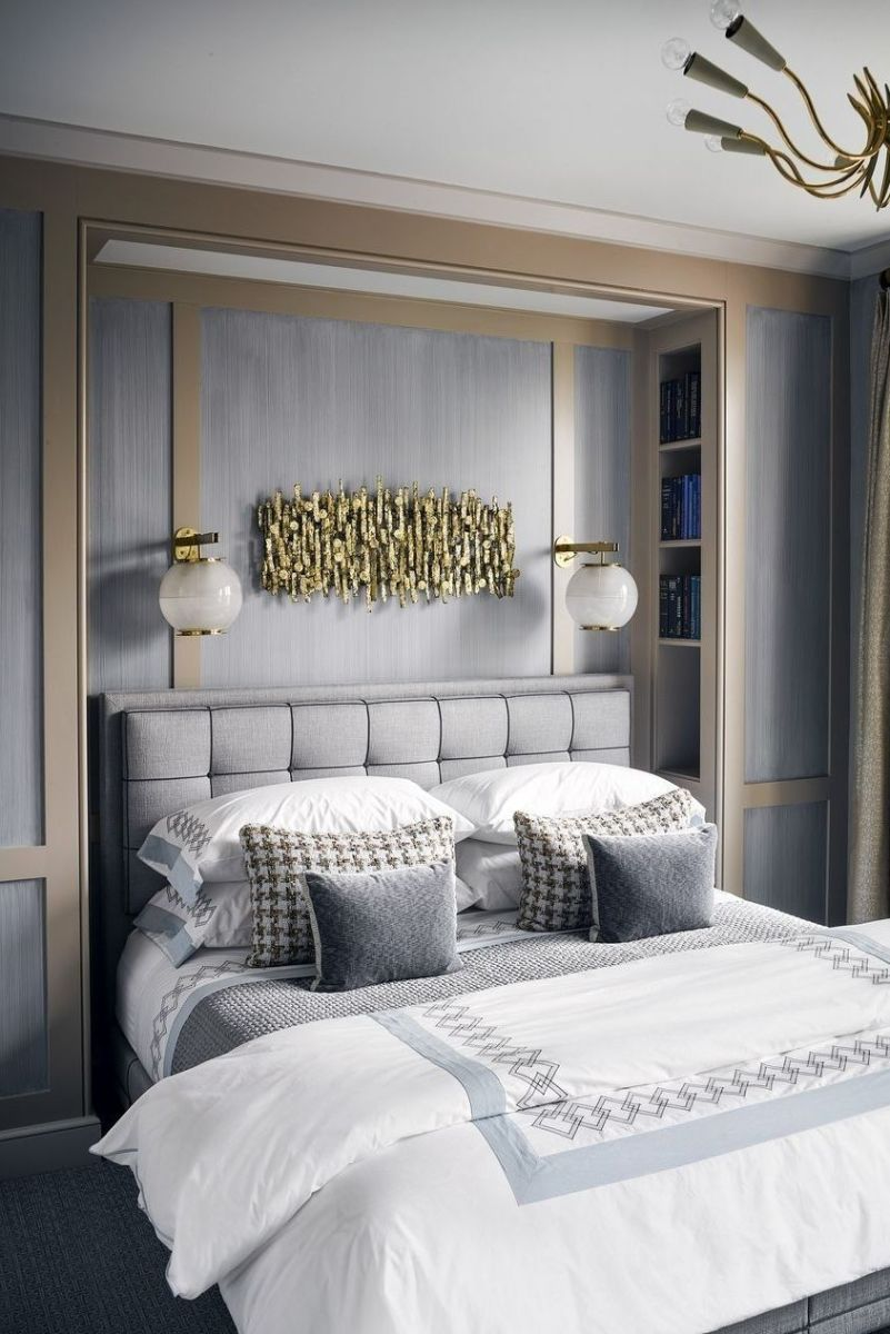 The unique wall lighting and the chandelier on the ceiling above the bed.
