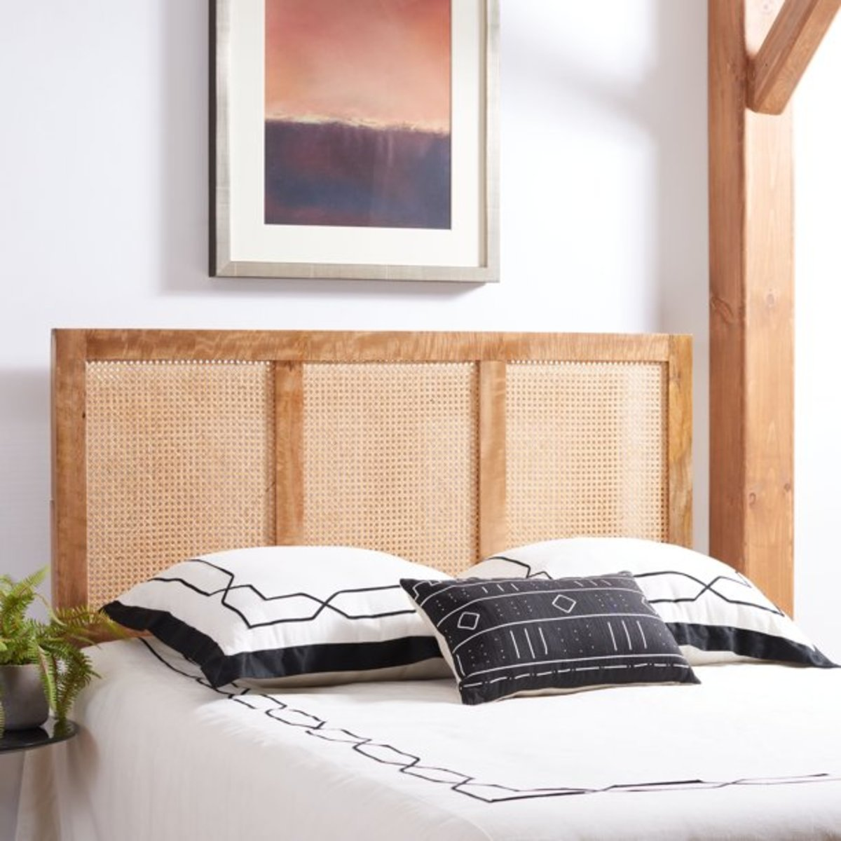 The lightweight cane with the wood frame is the headboard for the gorgeous bed.