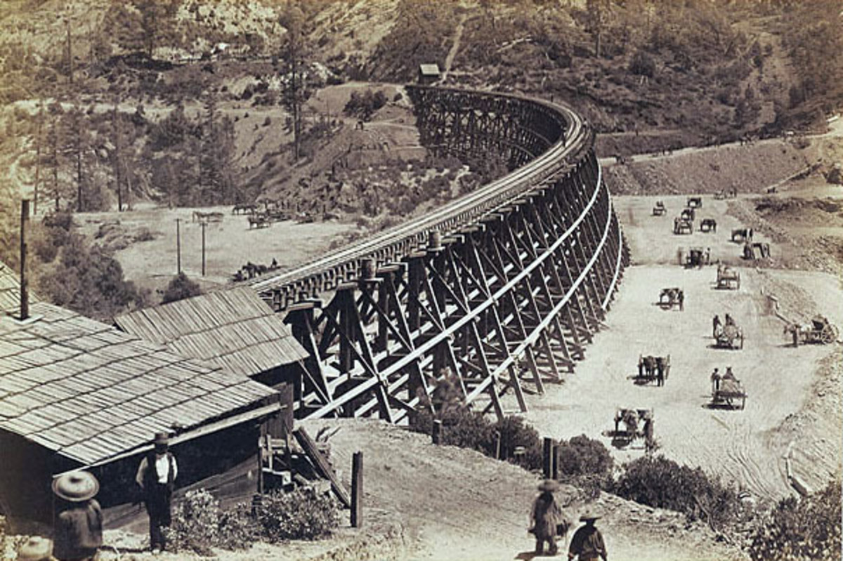 Chinese labourers shifting fill by hand next to a trestle. The fill would eventually replace the bridge.