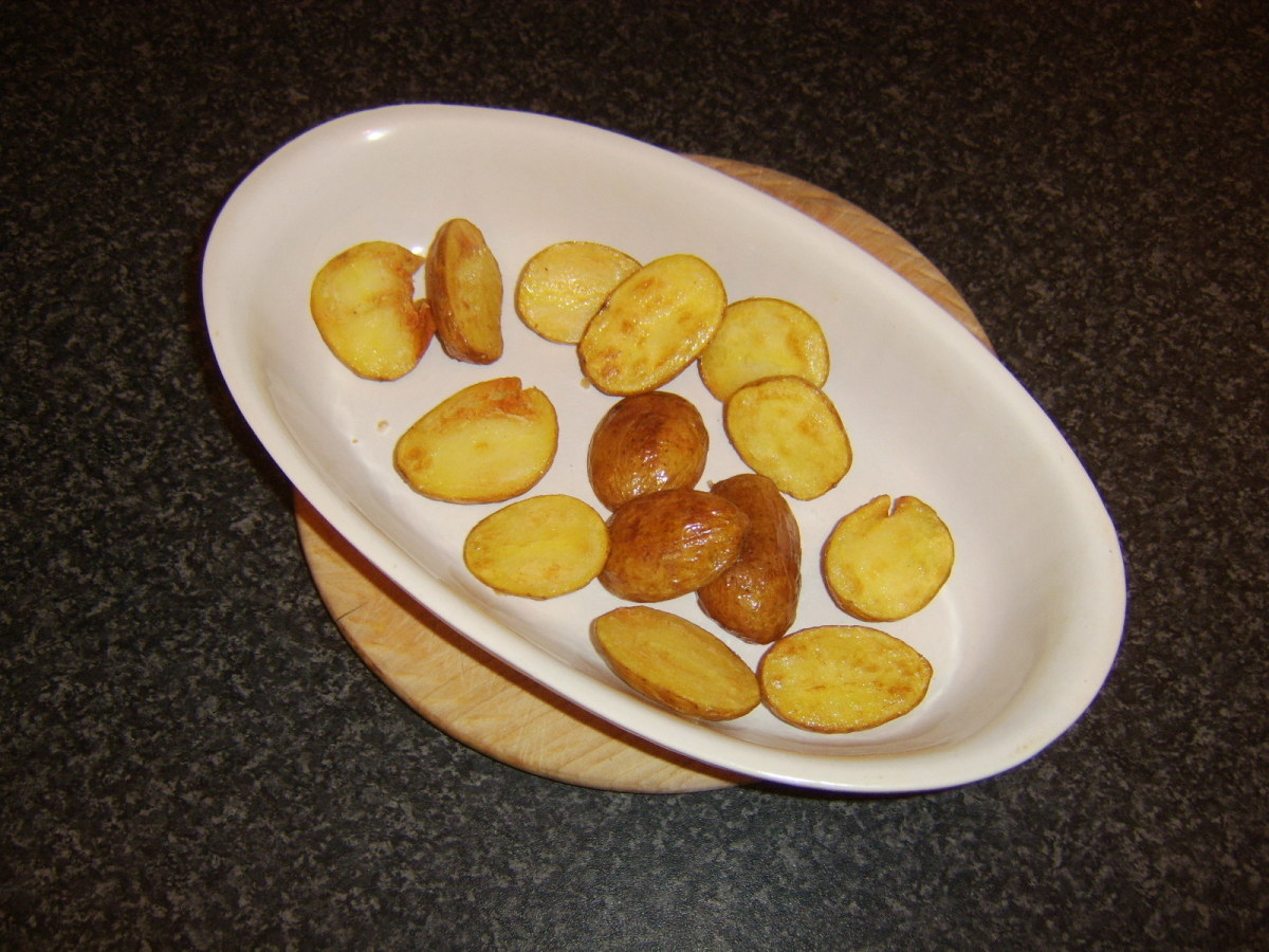Mini potato wedges are added to a warm dish and a low oven