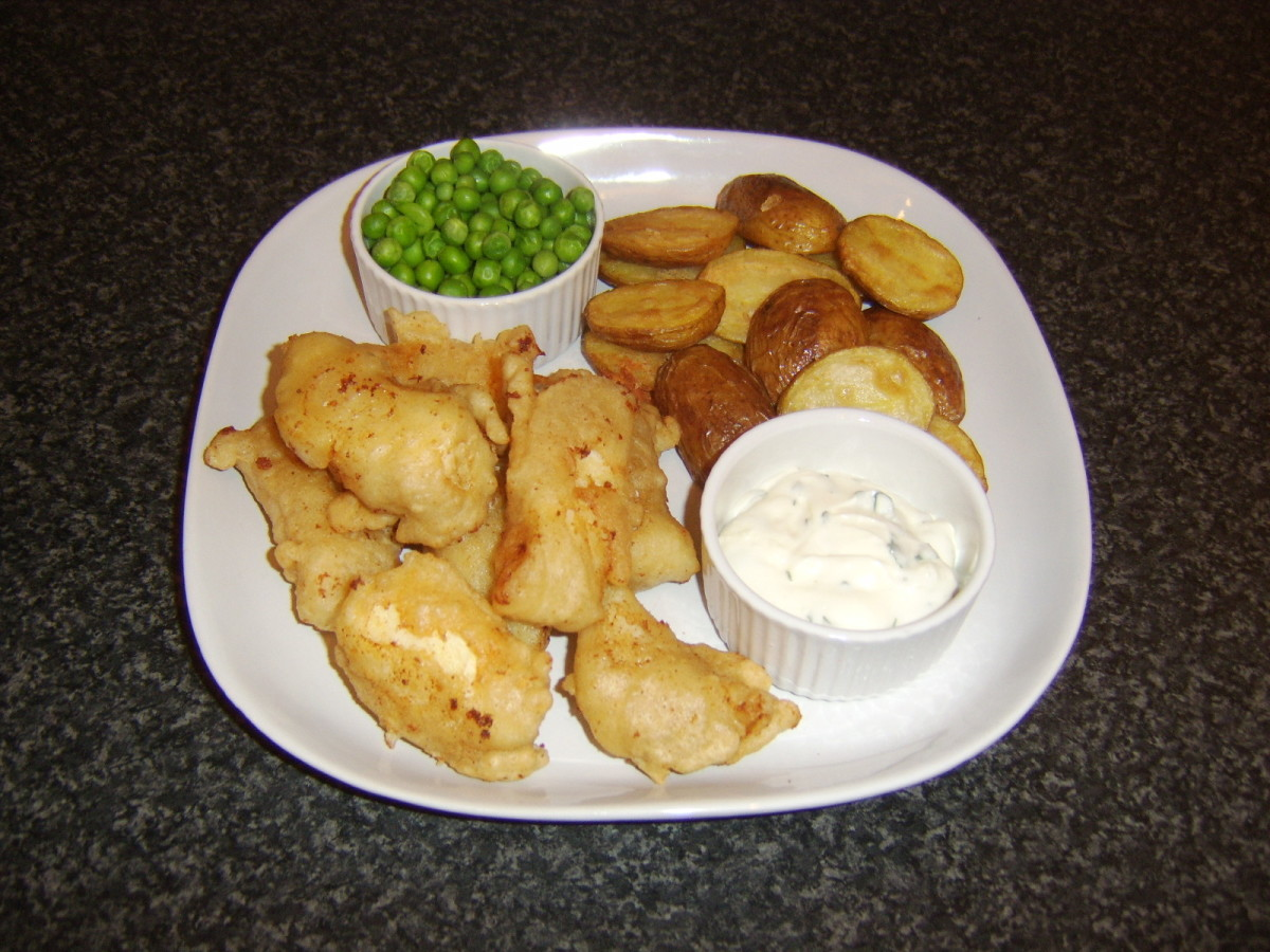 Goujons of battered cod are served with mini potato wedges, peas and a garlic mayo dip