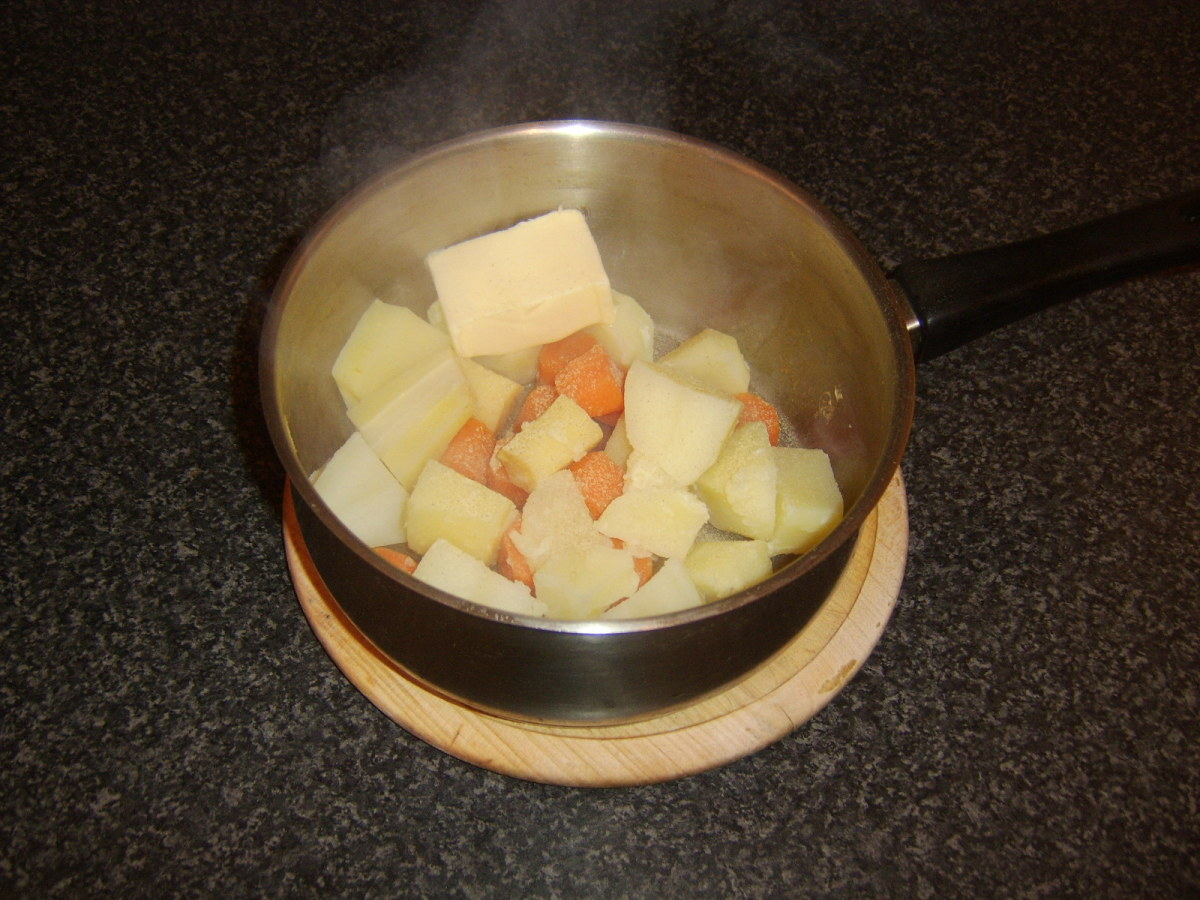 Butter and seasoning are added to vegetables for mashing