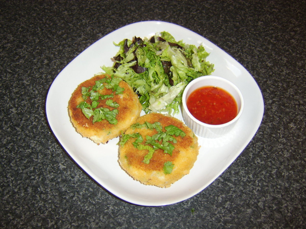 Spicy cod fish cakes are served with a simple leafy salad and a sweet chilli sauce dip