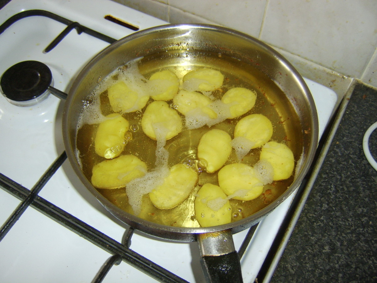 Potato halves are given first fry