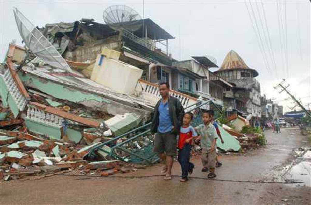 Three boys walk with their father through streets ruined by an earthquake that struck Gunung Sitoli on Nias Island, Indonesia, in March 2005
