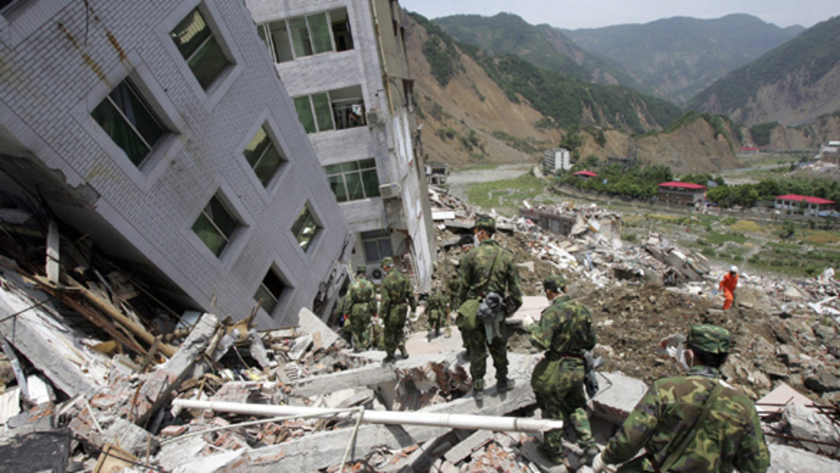 Chinese soldiers walk over collapsed buildings in search of earthquake victims in Beichuan, China, in May, 2008