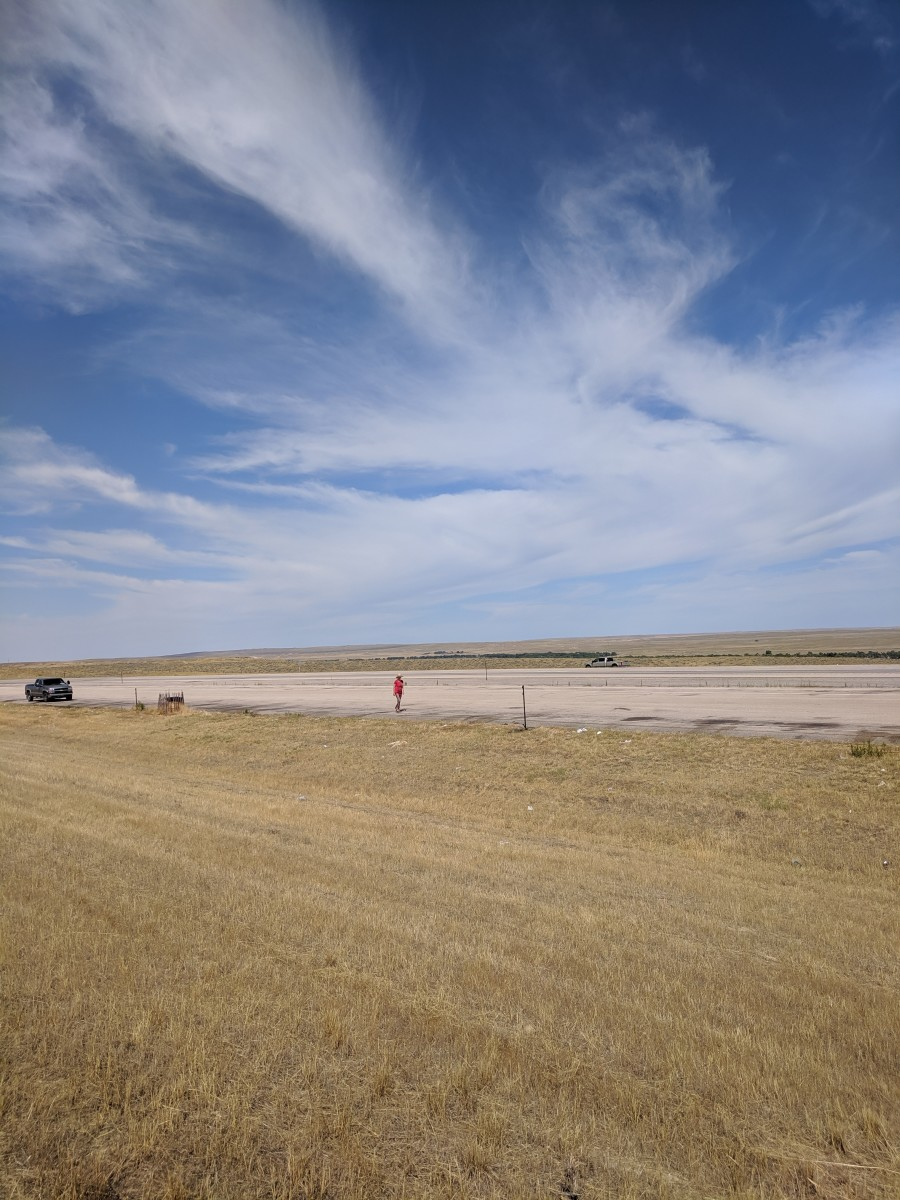 My wife and car dwarfed in the midst of the Great Plains in Wyoming.