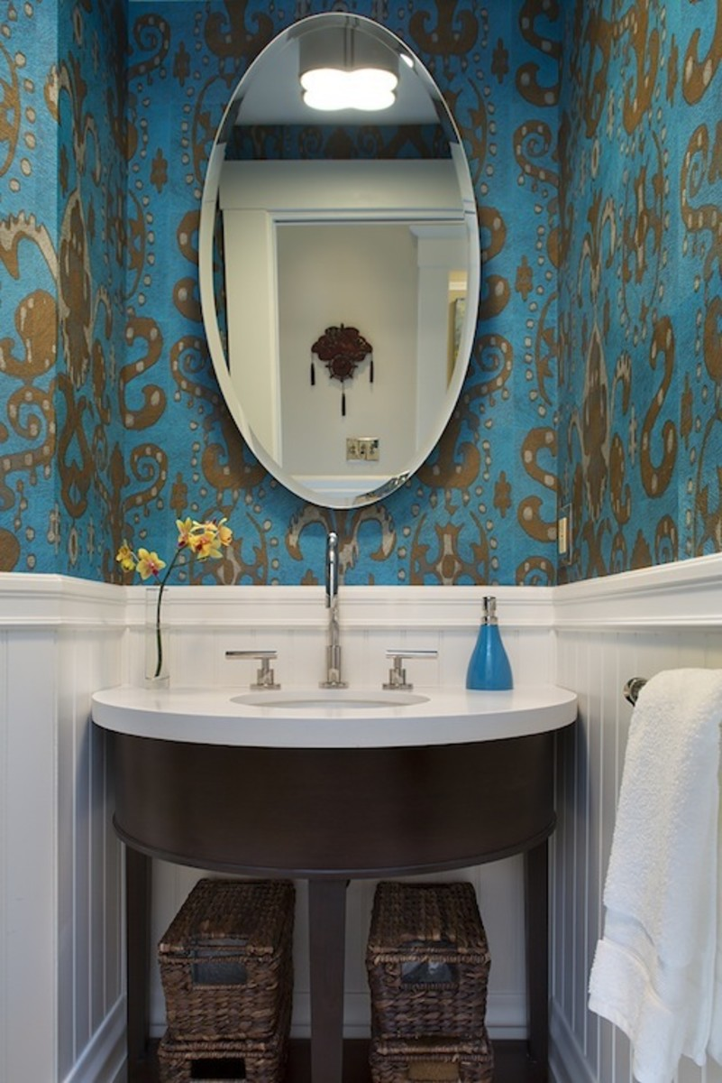 A  blue powder room with a half-wall of white beadboard and ikat wallpaper in shiny gold and peacock blue. A demi-lune vanity with white counter sink with sleek faucet sits under a oval mirror in the bathroom.