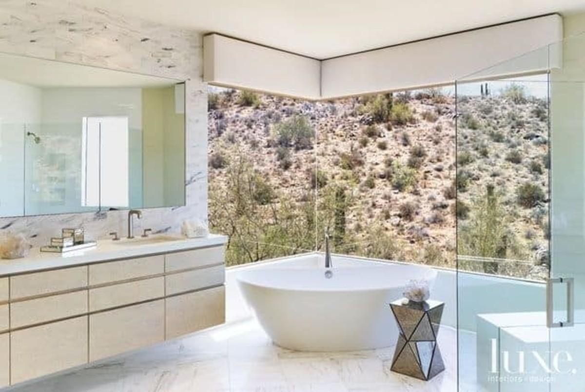 Tumbleweeds rule in the backyard Scottsdale home. The luxury bath has  windows overlooking desert hills.