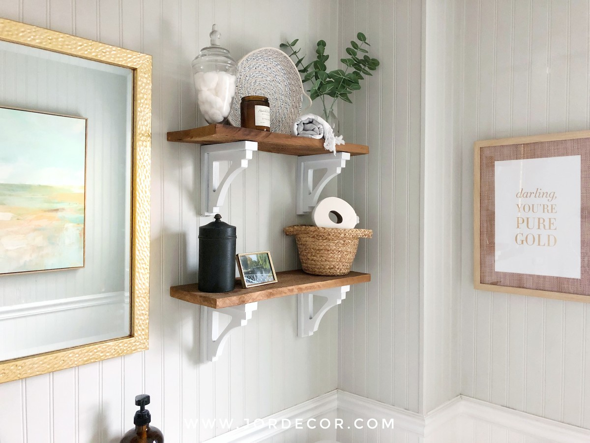 If you've decided on your bathroom wall shelves, style them by combining a few nice things that also serve as storage.