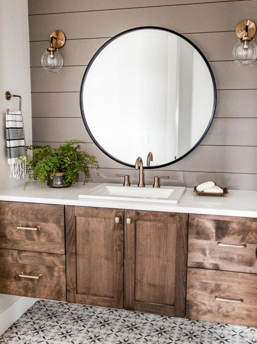 The rustic wood vanity and the gray shiplap and the round mirror and the bronze round sconces.