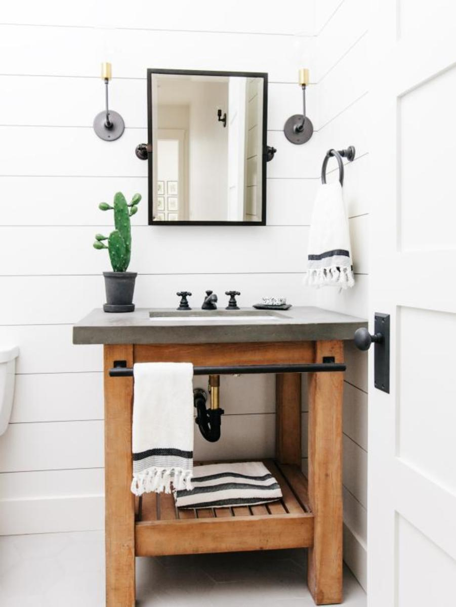 This powder bathroom with wood vanity, black and sconces with the white shiplap.