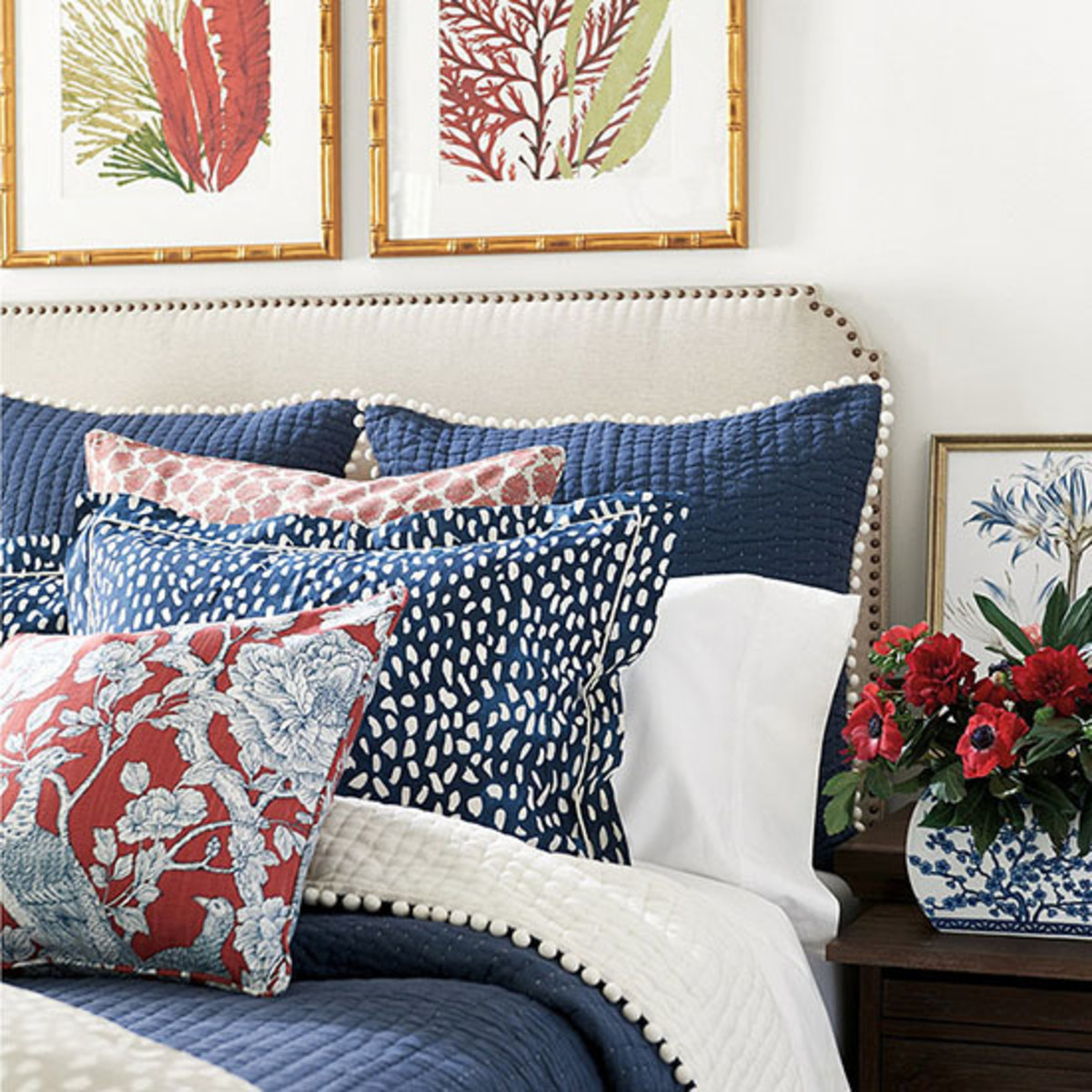 The bold bedroom in white, blue and red colors! The the furniture and linen tufted headboard and the sides.