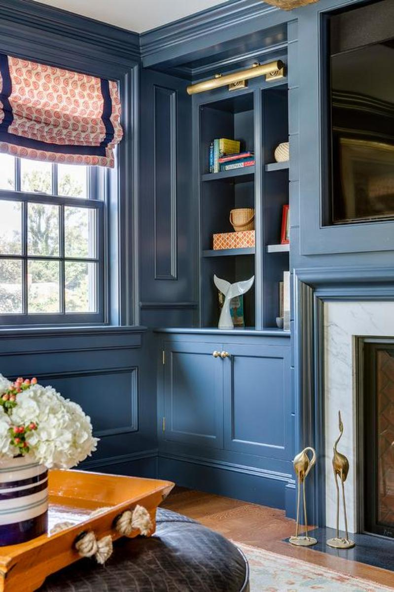 The living room is painted in the same beautiful blue as the rest of the house. The storage-inspired conventional living room blue cabinets and panel walls.