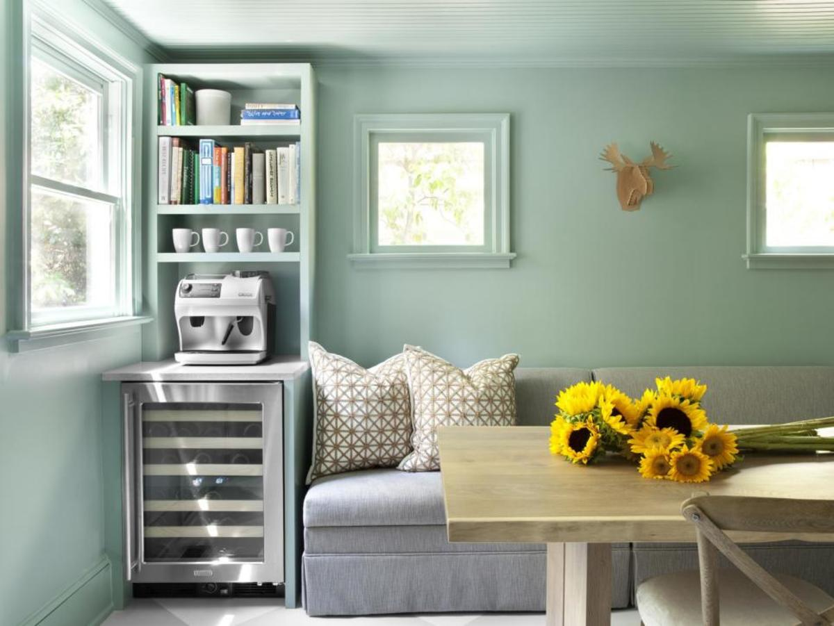The mint wall paint! A table and gray sofa in a cozy retro coffee and a wine fridge.