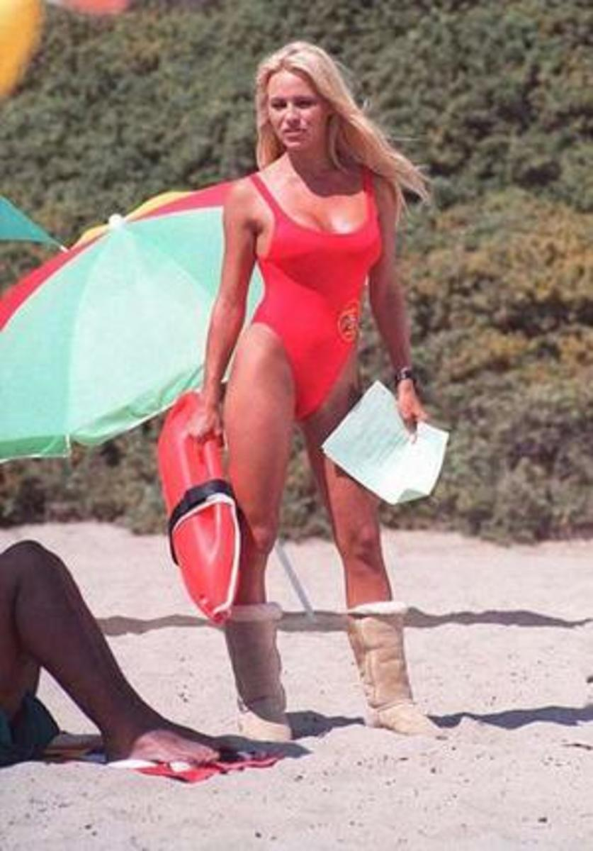 Bay Watch blond babe in red swim suite sporting Uggs and surfboard and life saving tube on the beach