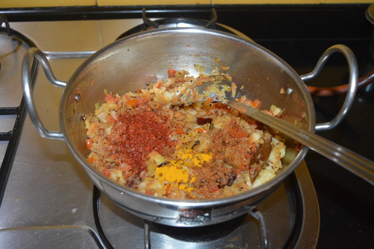 Step three: Lower the heat. Add red chili powder, garam masala powder, coriander powder, and turmeric powder.