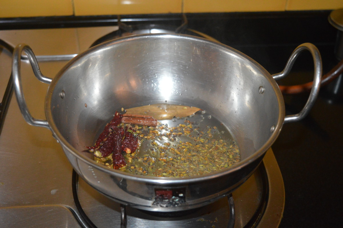 Step one: Heat oil in a deep-bottomed pan. Add the mustard seeds and allow them to crackle. Add fenugreek seeds, cumin seeds, fennel seeds, bay leaf, cinnamon stick, cloves, and broken red chilies. Saute on low heat for 30 seconds.