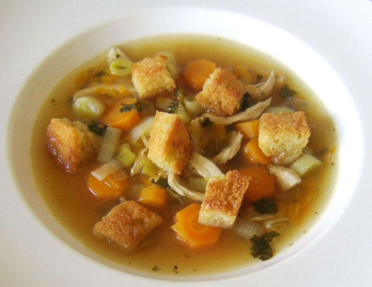 Croutons are scattered on the chicken, vegetable and nettle soup for service