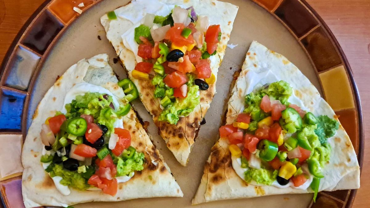 Loaded quesadillas with sour cream, guacamole, pico de gallo, and peppers