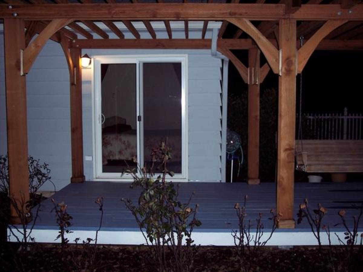 "A bedroom window was replaced with a sliding glass door out onto the recycled deck.  The addition of a pergola makes it a cozy outdoor ""room""."