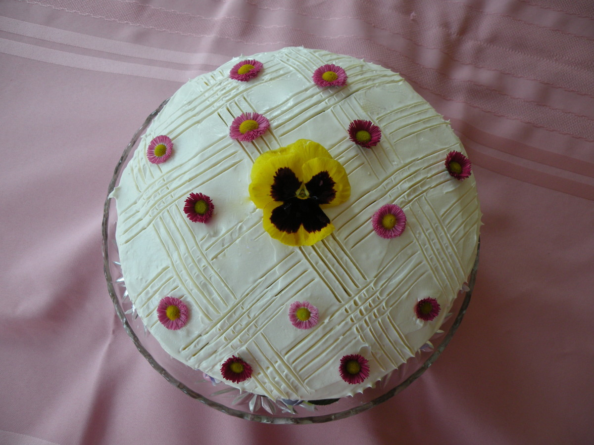 English daisies and a yellow pansy decorate this cake.