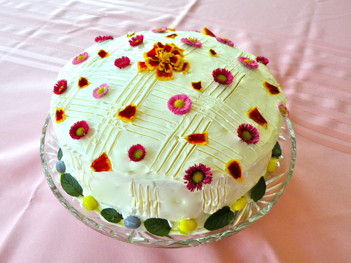 English Daisies are strewn over cake top along with petals from a marigold. A full marigold is used in the center.