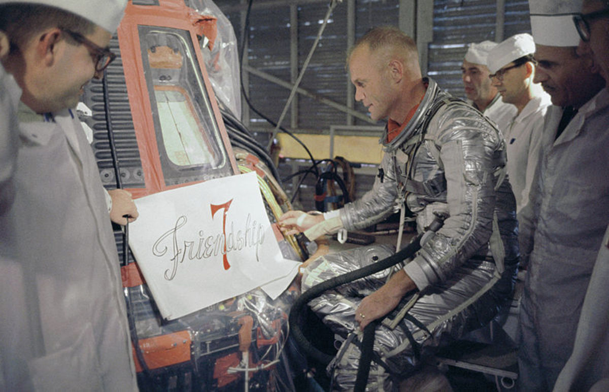 John Glenn and NASA technicians look at the  artwork to be painted on his Mercury capsule.
