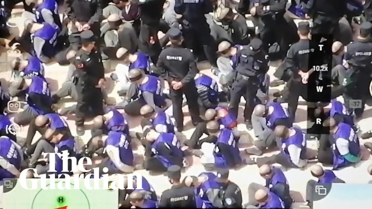 Uighurs with Heads Shaved, Blindfolded and Shackled, ready to loaded onto Cattle Cars