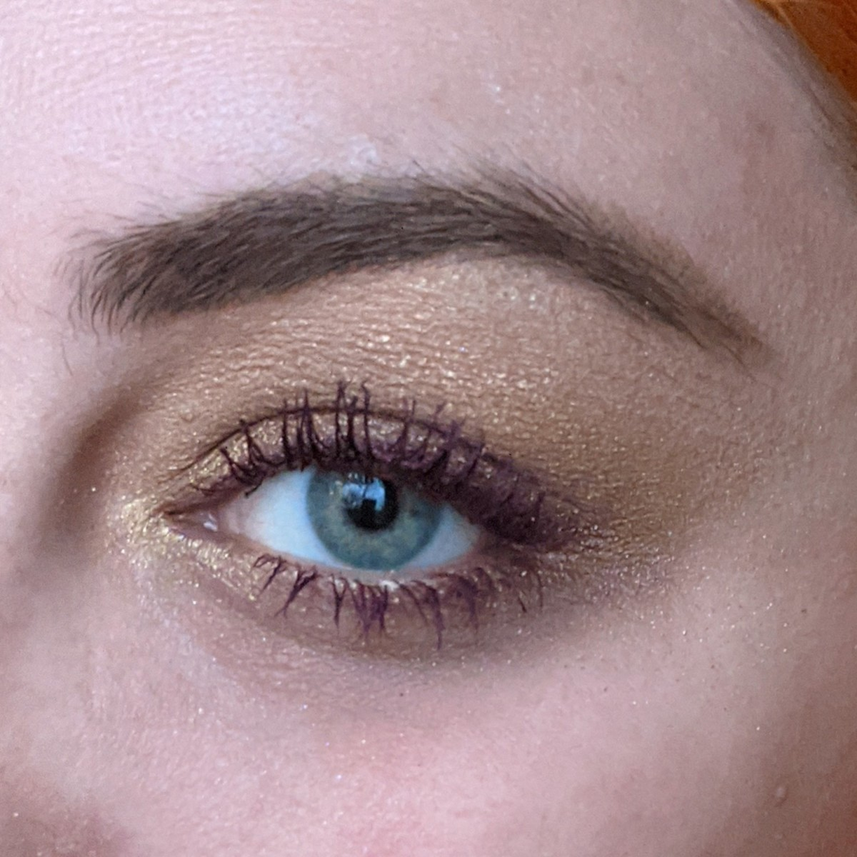 A complementary color look of gold and purple on my eye, using the Urban Decan Naked Honey Palette with L'Oreal Volumizing Mascara in Deep Purple.