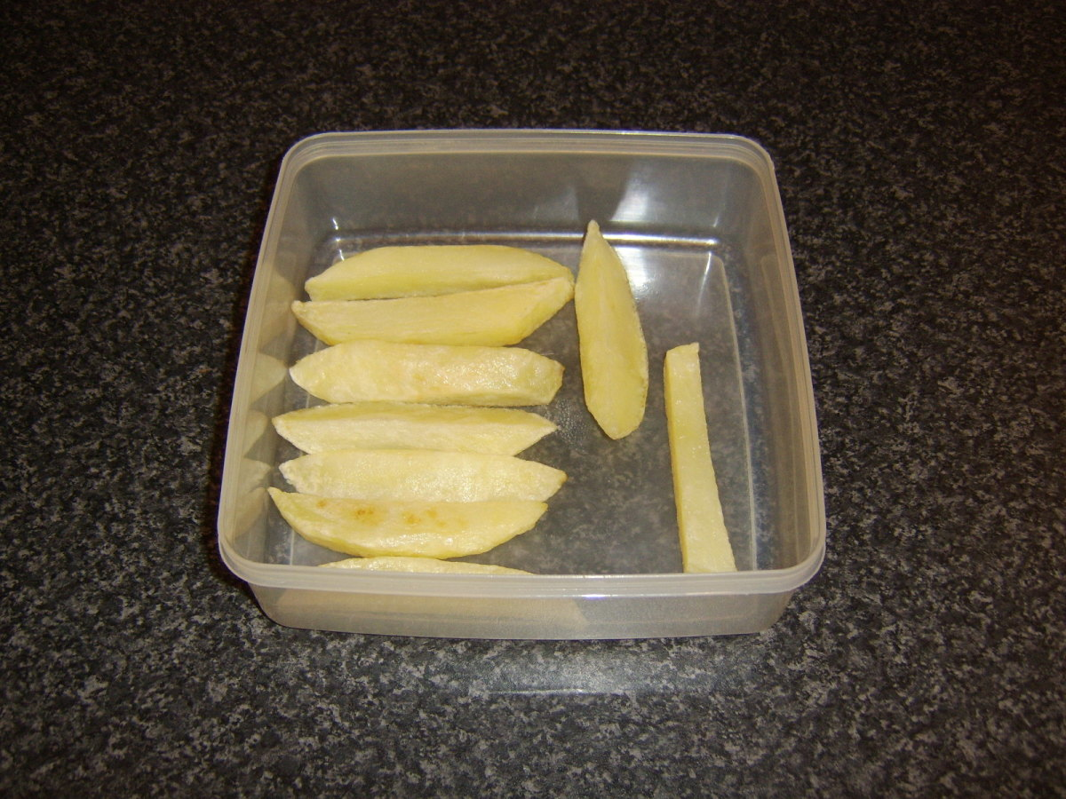The once fried chips are returned to the plastic dish and the fridge