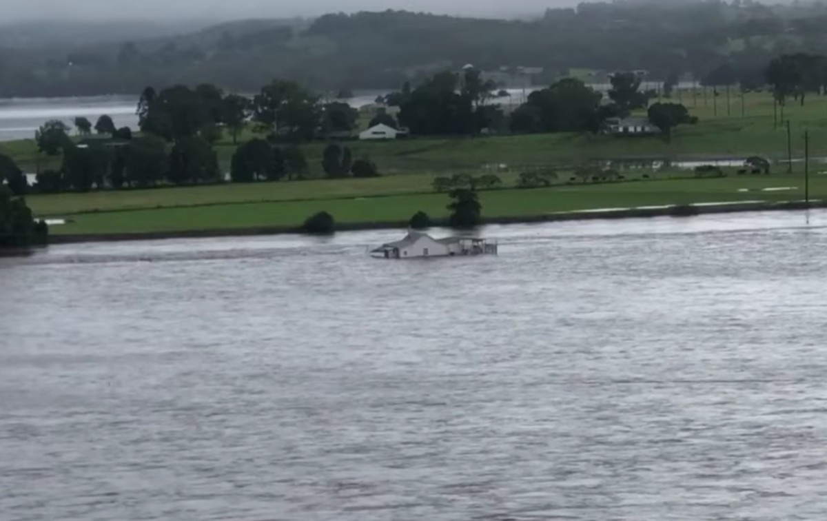 The farm house continues to float down Manning River.