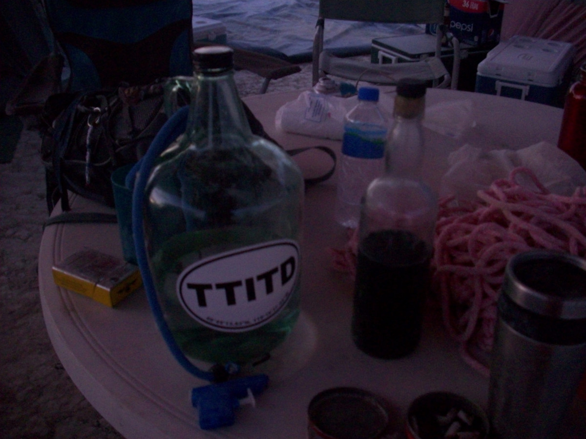 The table at our camp holding all the necessities, backpack, water, cup, booze, rope, cigarettes, bungee cord, and squirt gun.