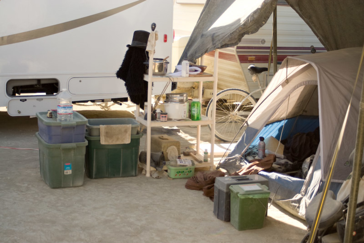 A nice set up. Tent under a shade structure with all supplies in storage bins to keep them handy and clean. Other items are handy on a shelf.
