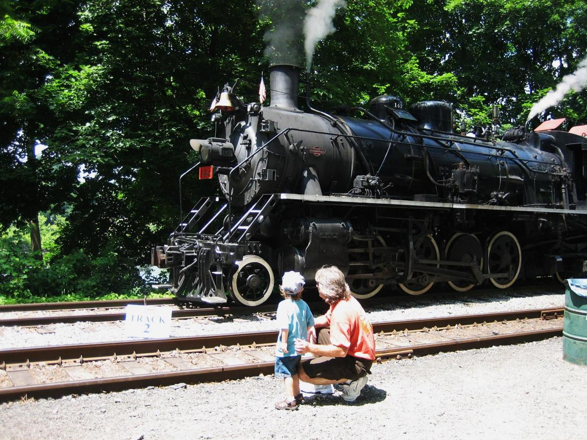 My son looking at the cool steam engine with Daddy