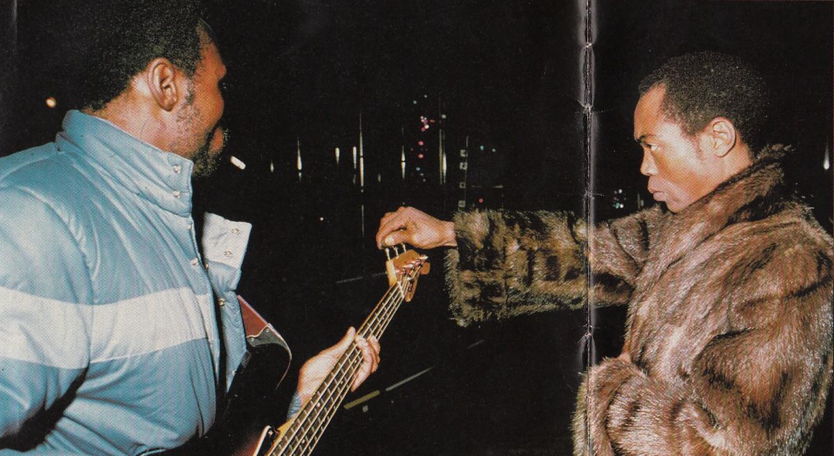 Fela helping a band member tun-up his guitar
