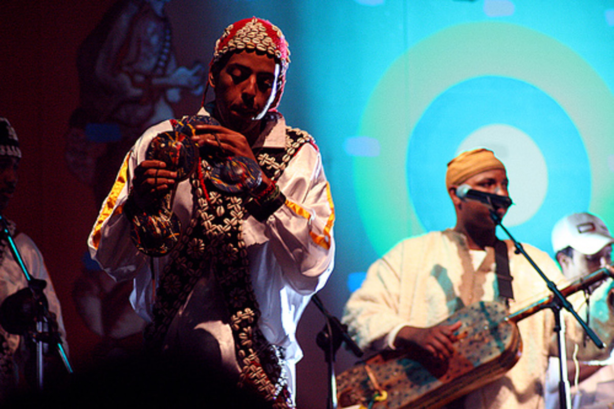 Gnawa Musicians in Essaouira, Morocco. Musician in the center is paying 'graqeb', large metal castanet-type things. The other instruments is a Hajoul(Hajhul), Guimbri or Sintir, a three stringed bass instrument with a camel skin covering its body