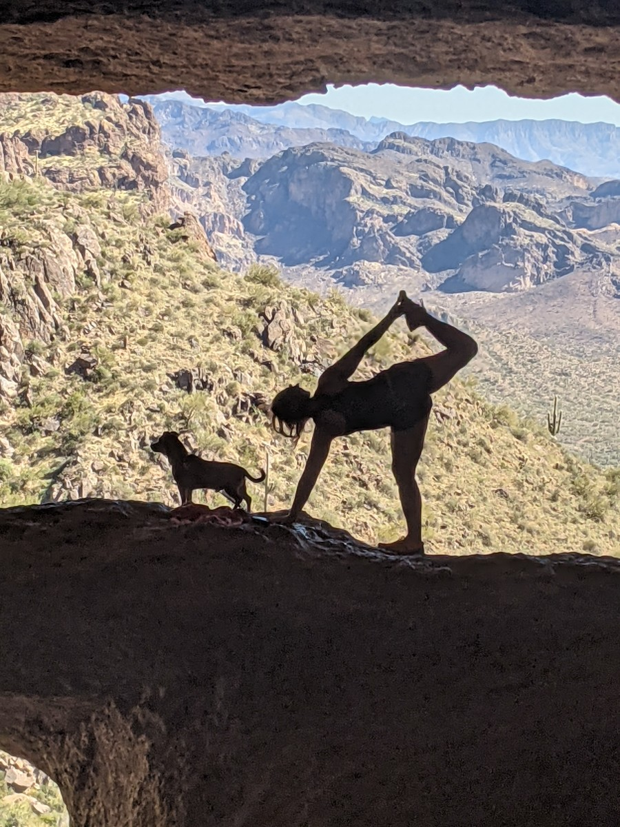 A visitor to Wave Cave doing a yoga position with her dog in the  rock across the front of Wave Cave