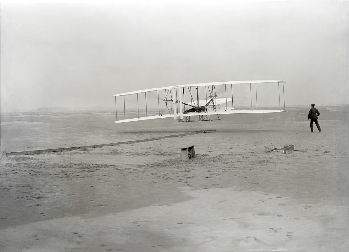 First flight of the Wright Flyer, December 17, 1903, Orville piloting, Wilbur running at wingtip