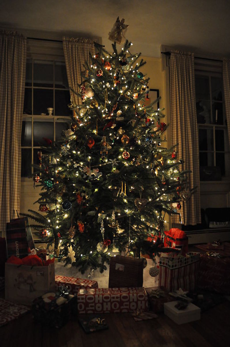 A Christmas tree is lit and decorated, surrounded by presents on Christmas Eve.